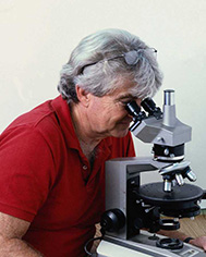A person sitting at a table with microscope Description generated with high confidence